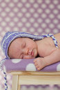 Little baby girl sleeping on a chair with hat Stock Photo