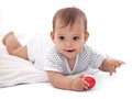 Little baby girl with small ball laying on the floor Stock Images