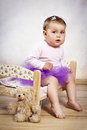 Little baby girl in tutu skirt sitting on the small bed Royalty Free Stock Photo