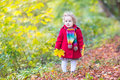 Little baby girl wearing red coat in autumn park beautiful with curly hair a an Royalty Free Stock Photos