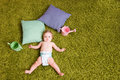 Little baby lies on green carpet