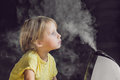 Little baby looks at the humidifier Royalty Free Stock Photo
