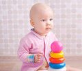 Little baby playing with toy colorful pyramid building Stock Images