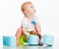 Little baby sitting on a pot and keeps the toilet paper studio photo Royalty Free Stock Photography