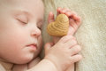 Little baby is sleeping with a wooden heart in hand girl Royalty Free Stock Photos