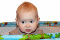 Little baby standing in the playpen in perplexity Royalty Free Stock Photo