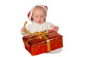 Little baby untying a Christmas gift Royalty Free Stock Photography