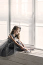 Little ballerina in gray dress puts on ballet shoes pointe front of the window Royalty Free Stock Images