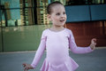 Little ballerina with pink costume bink smiling in front of a modern reflected building background Stock Photography