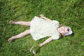 Little barefoot girl lies on green grass of meadow at summer sunny day Stock Photography