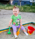 Little beautiful baby girl child plays bucket, rake and shovel in the sandbox sand smiling and showing its teeth Royalty Free Stock Photo