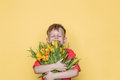 Little beautiful child with pink shirt gives a bouquet of flowers on Women`s Day, Mother`s Day. Birthday. Valentine`s day. Spring. Royalty Free Stock Photo
