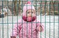 Little beautiful girl baby behind the fence, grid locked in a cap and a jacket with sad emotion on his face