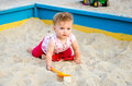 Little beautiful girl baby play in the sandbox and sand toys on the playground Royalty Free Stock Photo
