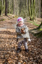 Little beautiful girl in a baby raincoat, hat and scarf is played in spring forest dry leaf litter throwing their smiles in a good Royalty Free Stock Photo