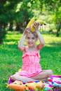 Little beautiful girl child kid sitting on grass with bananas Royalty Free Stock Photo