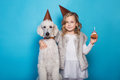Little beautiful girl with dog celebrate birthday. Friendship. Love. Cake with candle. Studio portrait over blue background Royalty Free Stock Photo