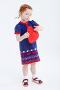 Little beautiful girl in dress plays with red heart at white background Stock Images