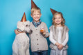 Little beautiful girl and handsome boy with dog celebrate birthday. Friendship. Family. Studio portrait over blue background Royalty Free Stock Photo