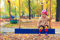 Little beautiful girl having fun on a swing in the Royalty Free Stock Photo