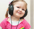 Little beautiful girl in headphones cute baby with looking at camera Royalty Free Stock Photo
