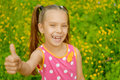 Little beautiful girl lifts thumb upwards and laughs against background of spring green park Royalty Free Stock Photography