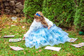 An little beautiful girl in a long blue dress sitting on the grass and playing with large game cards Royalty Free Stock Photo