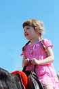 Little beautiful girl in pink dress sits on brown hors Royalty Free Stock Photo