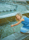 Little beautiful girl playing in fountain denim dress laughing and Stock Photo