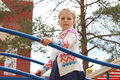 Little beautiful girl plays on children playground Royalty Free Stock Photo