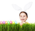Little beautiful girl with rabbit ears, green grass, colorful eggs.