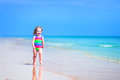 Little beautiful girl running on a beach happy laughing in colorful rainbow bathing suit and playing ocean coast in water splashes Royalty Free Stock Images