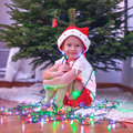 Little beautiful girl in santa claus hat sitting under the christmas tree among garlands this image has attached release Royalty Free Stock Image