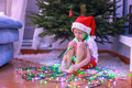 Little beautiful girl in santa claus hat sitting under the christmas tree among garlands this image has attached release Royalty Free Stock Images