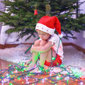 Little beautiful girl in santa claus hat sitting under the christmas tree among garlands this image has attached release Royalty Free Stock Photo