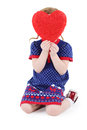 Little beautiful girl sits and hides her face behind red heart at white background Stock Photos