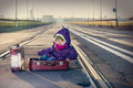 Little beautiful girl sitting in a suitcase near the railway Stock Images