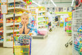 Little beautiful girl in supermarket modern with cart Stock Photography