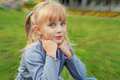 Little beautiful girl with tails sitting on the grass in the park Stock Image