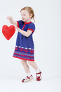 Little beautiful girl walks and holds red heart at white background Stock Photography