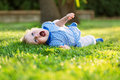 Little beautiful pretty happy girl lying on the grass and shouts Royalty Free Stock Photo