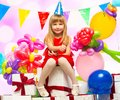 Little birthday girl in red dress sitting on gift boxes Stock Images