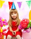 Little birthday girl in red dress sitting on gift boxes Royalty Free Stock Image