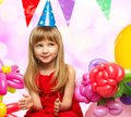 Little birthday girl in red dress sitting on gift boxes Royalty Free Stock Photography