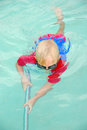 A little blond caucasian boy child in swimsuit cleaning the swimming pool with a brush under water to get ready for spring Royalty Free Stock Photo