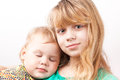 Little blond caucasian girl with sleeping sister portrait on white background Stock Images