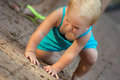 Little blond girl climbs on the ground in park Royalty Free Stock Photo