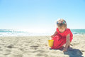 Little blond girl in red dress on the beach