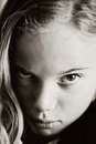 Little blond girl sad intense stare sepia slight digital grain added Stock Images
