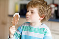 Little blond kid boy with curly hairs eating ice cream popsicle with chocolate at home Royalty Free Stock Photo